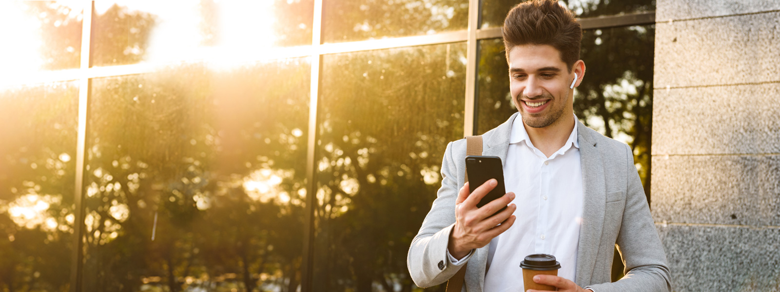 Man looking at phone, with airpod in his ear, standing in front of a building with the sun shining off the windows